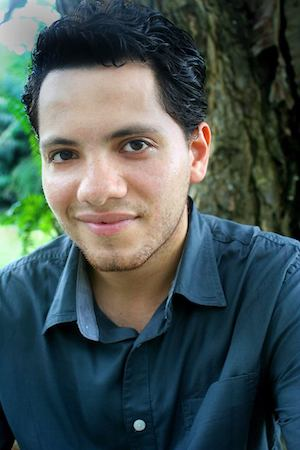 """Portrait of self-described """"Borinquén-Chapín-Bronx playwright,"""" Juan Ramirez Jr. He is sitting in front of a tree wearing a blue button down shirt."""